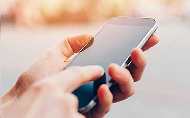 Hand som håller i mobiltelfon